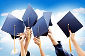 stock photo of outfits  - Unrecognizable group of people throwing graduations hats in the air - JPG