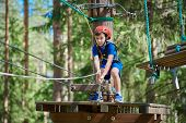 Cute Boy Enjoying Activity In Climbing Adventure Park At Sunny Summer Day. Safe Climbing With Helmet poster