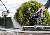Dslr Videography Slider In Action. Making Garden Maintenance Stock Videos. Modern Digital Technology poster