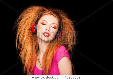 Cute Curly Blonde Girl Listening To Music On Big Red Headphones Isolated On Black