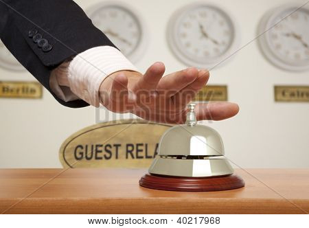 Hand of a businessman using a hotel bell
