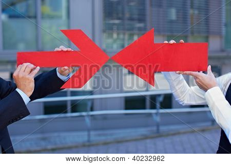 Business people holding two red arrows pointing to each other
