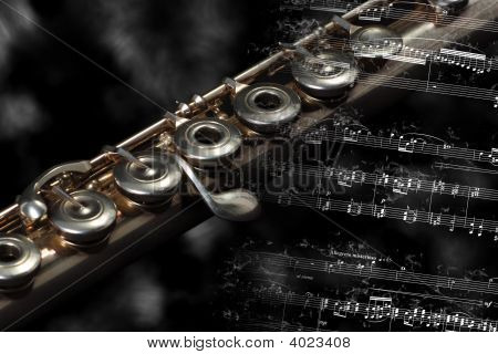 Silver Flute Instrument Resting On A Flaming Music Score