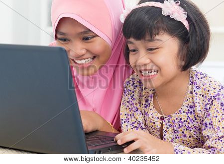 Southeast Asian females surfing internet at home. Malay Muslim girls.