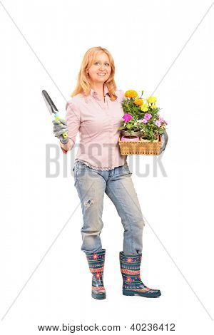 Full length portrait of a female gardener holding flowers and gardening equipment isolated on white background