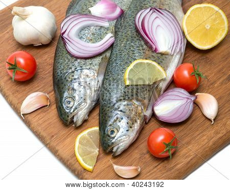 Trout, Vegetables And Lemon On A Cutting Board