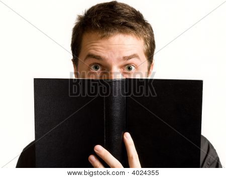 Eyes Of Surprised Man Above Black Book