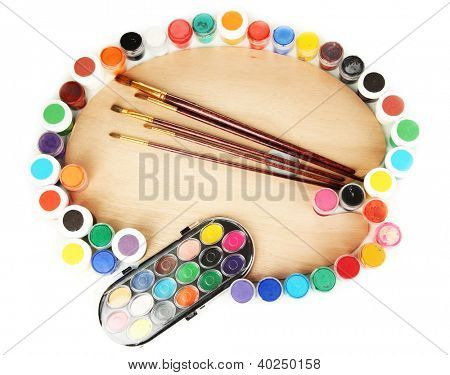 Wooden art palette with brushes for painting and paints isolated on white