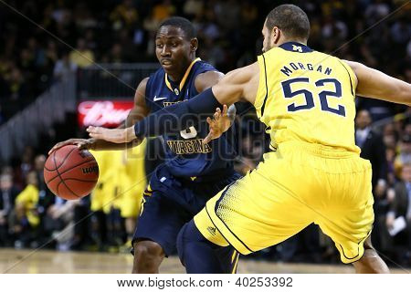 BROOKLYN-DEC 15: West Virginia Mountaineers guard Juwan Staten (3) dribbles past Michigan Wolverines forward Jordan Morgan (52) at Barclays Center on December 15, 2012 in Brooklyn.