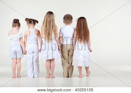 Back of four cute little girls and one boy in white clothes standing and holding hands.
