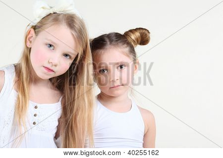 Two little funny and serious girl in white clothes look at camera. Focus on left girl.