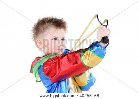 Boy in clown costume holds slingshot and aims up isolated on white background.