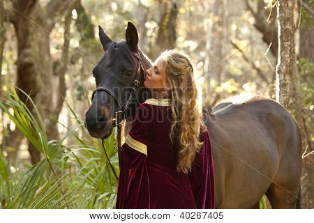woman in medieval dress with horse in forest