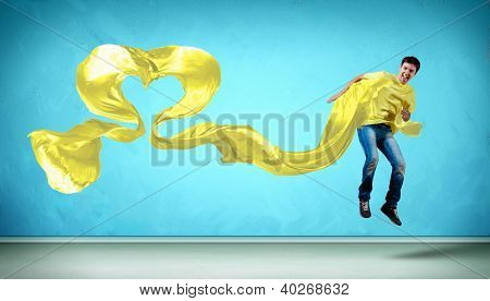 Young man dancing with yellow fabric over blue background