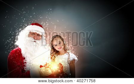 Portrait of Santa Claus with a little girl looking at a gift
