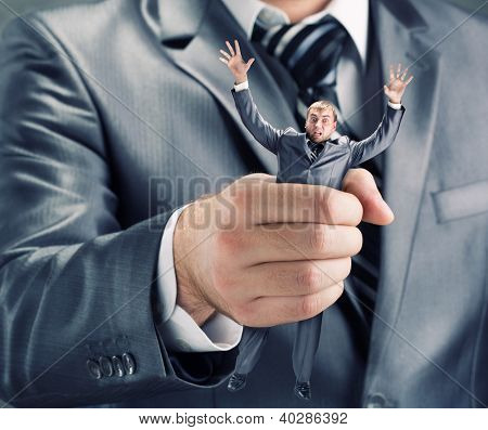 Squeezing small businessman in hand