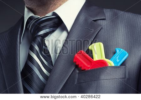 Businessman with colorful toy keys in suit pocket