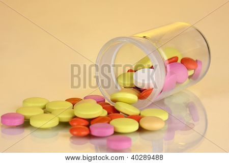 Pills in receptacle on yellow background