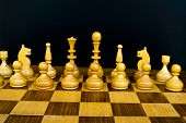 stock photo of draught-board  - Woody board with black and white chess figures - JPG