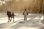stock photo of bareback  - two women riding horseback on the beach - JPG