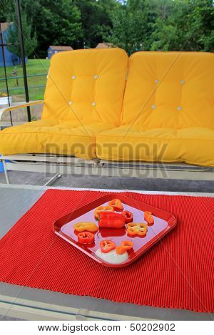 Red placemat with cut peppers and yellow couch