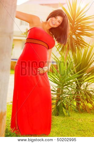 Happy expectant female having fun outdoors, fashion for pregnant young woman, exotic nature, summer joy, new life concept