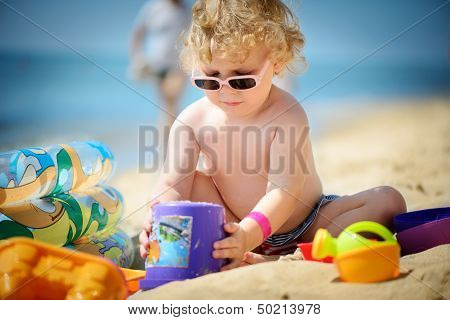 Cute Little Girl In Sunglasses Playing With Sand
