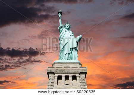 An upshot of the statue of liberty with sunset sky.