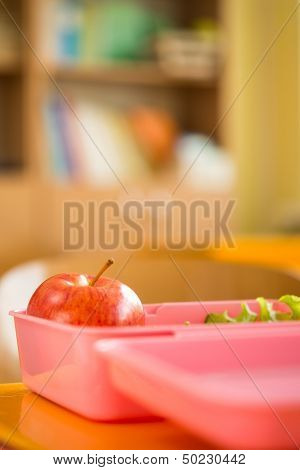 Food container with apple and salad in classroom