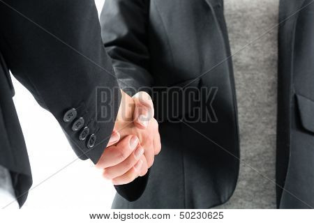 Young women in front of white background, they introduce themselves giving a handshake
