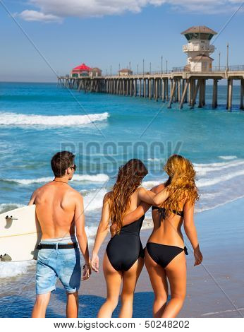 Teen surfers group of boys and girls walking rear view on Huntington beach California [ photo-illustration]