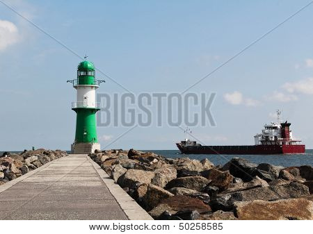 Green and white lighthouse and cargo ship leaving port