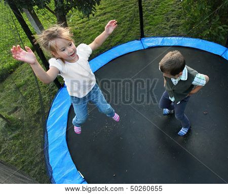 Two funny kids jumping on a outdoor trampoline.