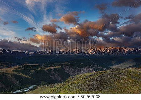Mountain landscape with river and snowy peaks at sunrise