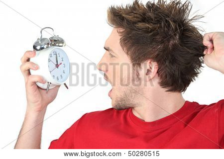 Man screaming with alarm clock in hand