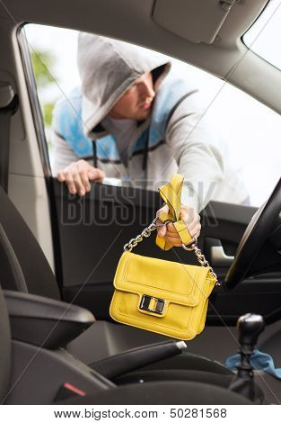transportation, crime and ownership concept - thief stealing bag from the car
