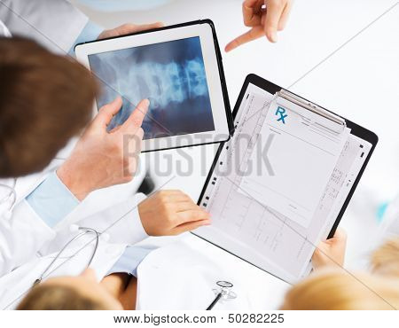healthcare, hospital and medical concept - group of doctors looking at x-ray on tablet pc
