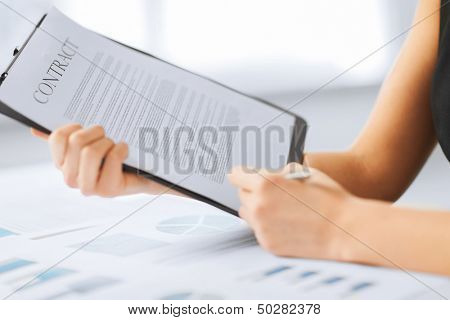 business, office, law and legal concept - picture of woman hand signing contract paper