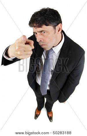 Humorous high angle portrait of a man in a business suit pointing a finger in accusation and blame with a stern uncompromising expression isolated on white