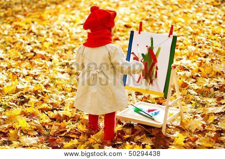 Child Drawing On Easel In Autumn Park. Creative Kids Development Concept.