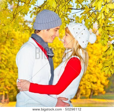 Happy couple in fall under leaves of a broad leaved lime. Autumn set.