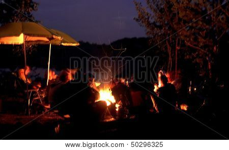 Group of people relaxing near campfire. Blur effect