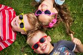 stock photo of cute innocent  - Cheerful kids laying on a grass - JPG
