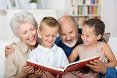 stock photo of babysitting  - Cute boy and girl sitting in the lap of their grandparents and looking happily together at a photo album - JPG