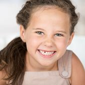 stock photo of tooth gap  - Adorable beautiful little girl grinning at the camera showing off her missing front tooth close up portrait - JPG