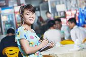 stock photo of chinese menu  - young Chinese waitress girl of street restaurant in china with menu waiting an order - JPG