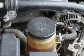 pic of lubricant  - Power steering fluid cap with warning label in a car - JPG