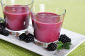 stock photo of blackberries  - Blackberry smoothie with fresh blackberries on green background - JPG