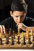 picture of 11 year old  - An 11 year old boy making a moving during a chess game with a sly look - JPG
