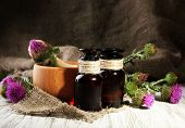 stock photo of scottish thistle  - Medicine bottles and mortar with thistle flowers  - JPG
